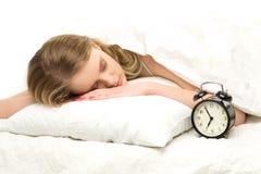 Mujer durmiente con el reloj de alarma Imagenes de archivo