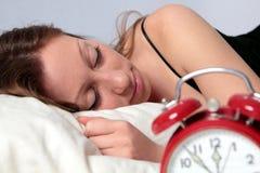 Mujer durmiente con el reloj de alarma Foto de archivo