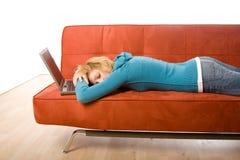 Mujer durmiente con la computadora portátil Imagenes de archivo