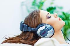 Mujer durmiente en casa con los auriculares Foto de archivo libre de regalías