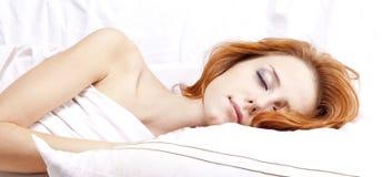 Mujer durmiente en whitelying en la cama Imagen de archivo