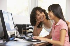 Mujer e hija adolescente que usa el ordenador Imagenes de archivo