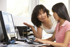 Mujer e hija adolescente que usa el ordenador Imagen de archivo libre de regalías