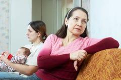 Mujer e hija maduras con el bebé que tiene conflicto Imágenes de archivo libres de regalías