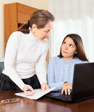 Mujer e hija maduras en la tabla con el ordenador portátil Foto de archivo libre de regalías