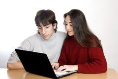Mujer e hijo que miran la computadora portátil Foto de archivo libre de regalías