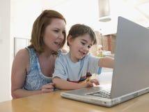Mujer e hijo que usa el ordenador portátil en la tabla Fotos de archivo libres de regalías