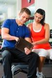 Mujer e instructor personal en gimnasio, con pesas de gimnasia Imagenes de archivo