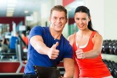 Mujer e instructor personal en gimnasio, con pesas de gimnasia imágenes de archivo libres de regalías
