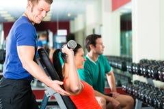 Mujer e instructor personal en gimnasio, con pesas de gimnasia imagen de archivo