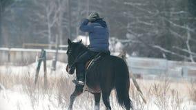 Mujer ecuestre en sombrero en el montar a caballo en campo nevoso almacen de metraje de vídeo