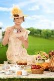 Mujer edwardian del vintage con el sombrero en la comida campestre imagen de archivo libre de regalías