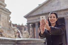 Mujer ejecutiva feliz que hace el selfie delante del panteón en la ROM Imagen de archivo libre de regalías