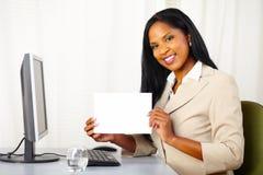 Mujer ejecutiva que muestra una tarjeta blanca Fotografía de archivo libre de regalías