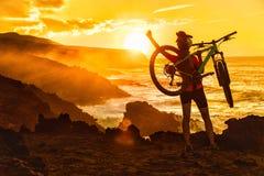 Mujer el biking de montaña del éxito MTB en la puesta del sol de la naturaleza fotografía de archivo