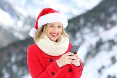 Mujer el días de fiesta de la Navidad usando el teléfono que le mira Imagenes de archivo