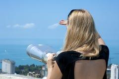 Mujer el las vacaciones que miran a través de los prismáticos Imagen de archivo libre de regalías