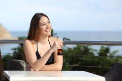 Mujer el vacaciones que bebe en una terraza del hotel Fotografía de archivo