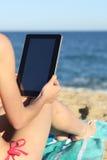 Mujer el vacaciones que lee una tableta en la playa Imagen de archivo