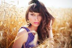 Mujer el viento en su pelo en un campo de trigo Imágenes de archivo libres de regalías
