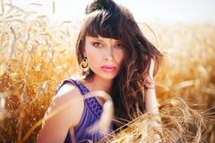 Mujer el viento en su pelo en un campo de trigo Foto de archivo libre de regalías