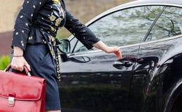 Mujer elegante adulta de Youn con la puerta abierta de la maleta roja en el lujo c Imagen de archivo