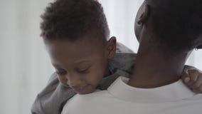 Mujer elegante afroamericana en la blusa blanca que adquiere las manos a su muchacho juguetón divertido del niño en sala de est almacen de metraje de vídeo