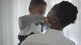 Mujer elegante afroamericana en la blusa blanca que adquiere las manos a su muchacho juguetón divertido del niño en sala de est metrajes