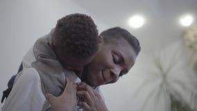 Mujer elegante afroamericana en la blusa blanca que adquiere la parte posterior a su muchacho juguetón divertido del niño en sala metrajes
