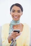 Mujer elegante alegre que se sienta en envío de mensajes de texto del sofá Foto de archivo libre de regalías