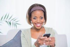 Mujer elegante alegre que se sienta en envío de mensajes de texto del sofá Fotos de archivo