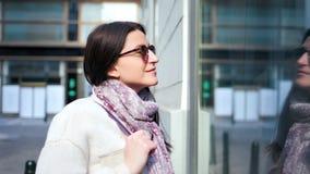 Mujer elegante bonita que sonríe y que mira en el escaparate de cristal del primer medio de la tienda de moda almacen de metraje de vídeo