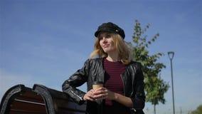 Mujer elegante con café en un banco almacen de video