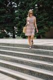 Mujer elegante con el café a ir a caminar abajo de los pasos en parque Foto de archivo libre de regalías