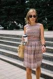 Mujer elegante con el café a ir a caminar abajo de los pasos en parque Imagen de archivo