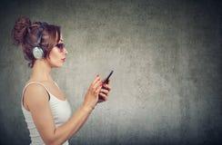 Mujer elegante con el teléfono que escucha la música fotografía de archivo