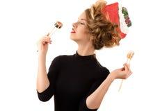 Mujer elegante con un peinado de moda que come los rollos Fotos de archivo