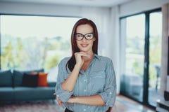 Mujer elegante confiada joven que presenta en sala de estar imagen de archivo libre de regalías