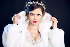 Mujer elegante de la belleza del invierno en el abrigo de pieles blanco Por del modelo de moda Imágenes de archivo libres de regalías