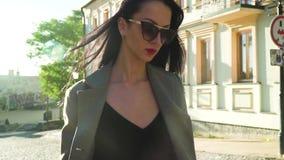 Mujer elegante de la elegancia en gafas de sol que camina en la calle en la cámara lenta almacen de metraje de vídeo