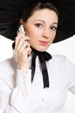 Mujer elegante de la sonrisa feliz joven con el teléfono móvil que lleva el vestido y el sombrero victorianos negros y blancos del Fotos de archivo libres de regalías