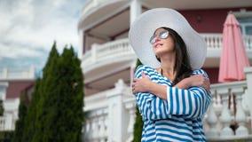 Mujer elegante del ángulo bajo en las gafas de sol y el sombrero que se colocan con las manos cruzadas que sonríe y que goza almacen de metraje de vídeo