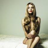 Mujer elegante desnuda en cama Imágenes de archivo libres de regalías