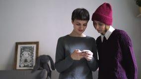 Mujer elegante dos que usa el teléfono móvil en el interior casero Smartphone femenino de los amigos almacen de video