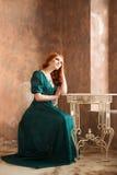 Mujer elegante en el estilo retro que se sienta en la tabla Mujer triste elegante en estilo retro depresión Foto de archivo