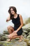 Mujer elegante en el vestido que se sienta en las rocas fotos de archivo