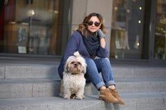 Mujer elegante en gafas de sol con el perro del shih-tzu que se sienta en los pasos Imágenes de archivo libres de regalías