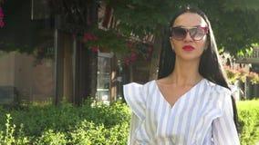Mujer elegante en gafas de sol y blusa pelada que camina en la cámara lenta en la calle metrajes