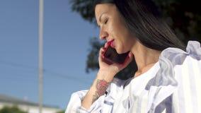 Mujer elegante en la blusa blanca que contesta a la llamada en su teléfono almacen de video