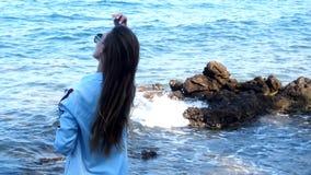 Mujer elegante en Rocky Sea Beach almacen de metraje de vídeo